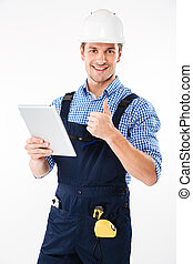 Happy male builder showing thumb up and holding pc tablet