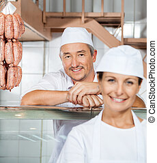 Happy Male Butcher With Colleague At Butchery