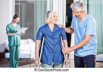 Happy Male Caretaker Helping Senior Woman In Walking