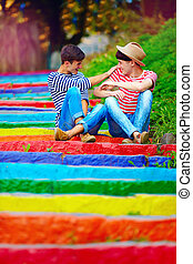 happy male couple having fun on rainbow stairs