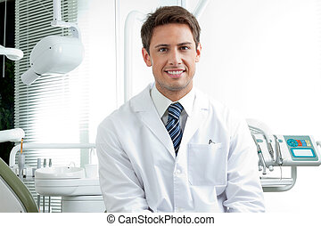 Portrait of happy male dentist wearing lab coat while sitting in clinic