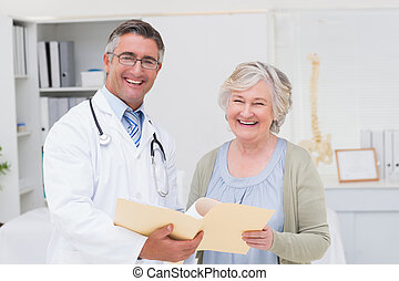 Happy male doctor and female patient with reports