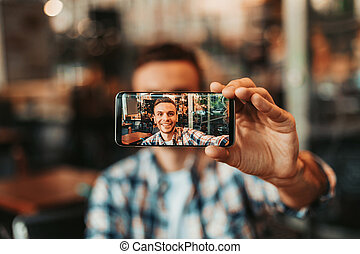 Happy male doing photo on phone inside