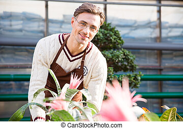 Happy male florist working with beautiful pink flowers