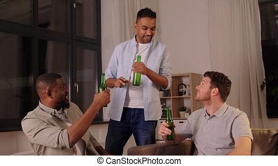 happy male friends drinking beer at home at night - ...