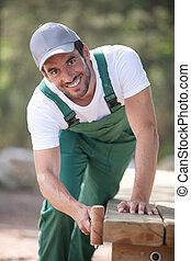 happy male gardener hammering on the garden