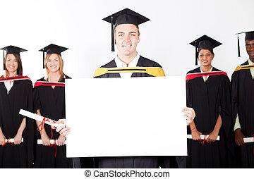 happy male graduate holding white board