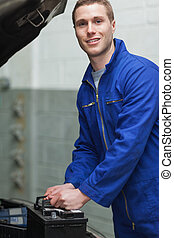 Happy male mechanic with car battery