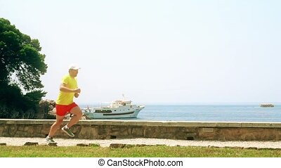 Happy male runner running at seaside, slow motion shot -...