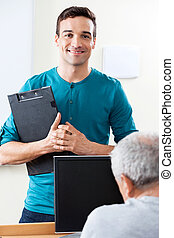Happy Male Teacher Holding Clipboard In Computer Class