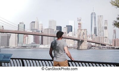 Happy male tourist comes up to epic Brooklyn Bridge river...