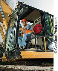 male worker operating excavator