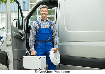Happy Male Worker With Wire And Toolbox In Front Of Van