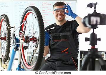 Happy man adjusting safety glasses and sitting near bicycle...