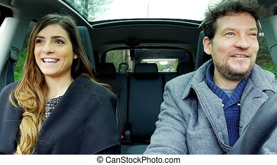 Happy man and beautiful woman in car driving talking smiling