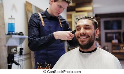 happy man and stylist doing haircut at barber shop - beauty,...