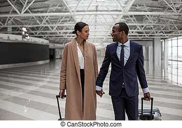 Happy man and woman are walking in terminal