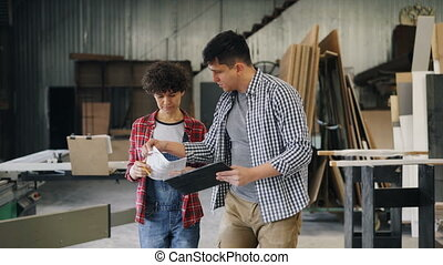 Happy man and woman discussing work in wood workshop holding...