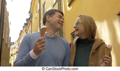 Happy man and woman eating ice-cream during a walk
