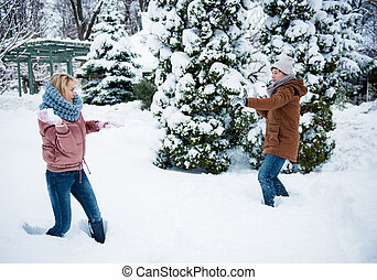 Happy man and woman having fun with snow in winter