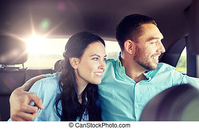 happy man and woman hugging on taxi back seat