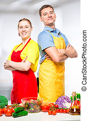 happy man and woman in aprons preparing vegetable salad, portrait in the kitchen