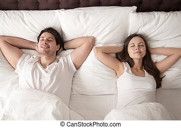 Happy man and woman lying in bed with eyes closed