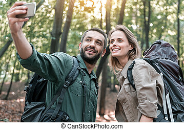 Happy man and woman photographing themselves on smartphone...