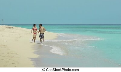 happy man and woman run on beach