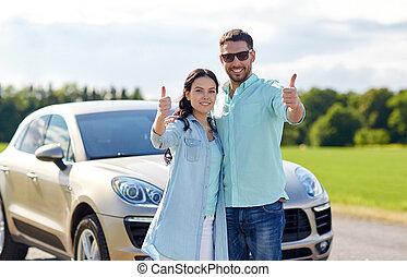 happy man and woman showing thumbs up at car