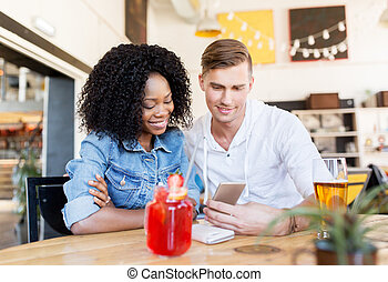 happy man and woman with smartphone at bar