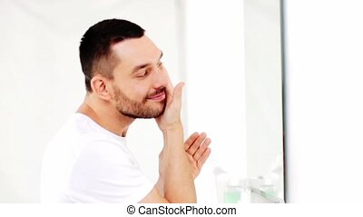 happy man applying aftershave to face at bathroom
