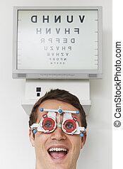 Happy Man At Optometrist Having Sight Test