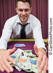 Happy man at poker table taking his winnings