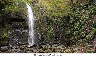 Happy man backpacker enjoying amazing tropical waterfall. Travel Lifestyle and success concept vacations into the wild nature on background mountain.