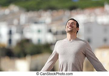 Happy man breathing deeply fresh air in a rural town