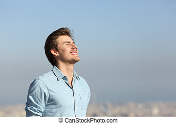 Happy man breathing deeply fresh air outskirts