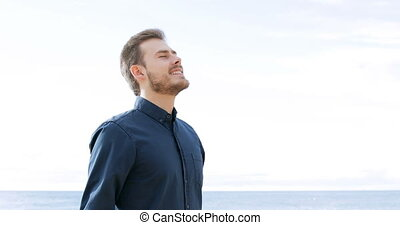 Happy man breathing fresh air on the beach