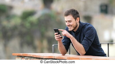 Happy man browsing phone content in a balcony - Happy man...