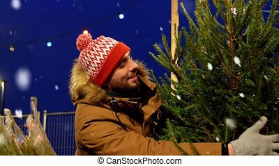 winter holidays and people concept - happy smiling man buying christmas tree at street market in evening over snow falling