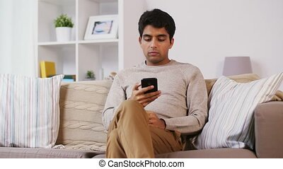 happy man calling on smartphone at home - technology,...
