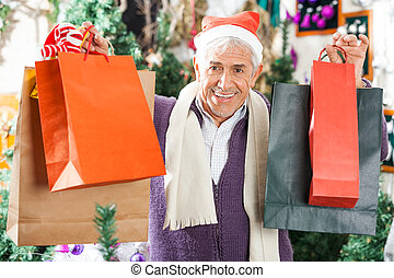 Happy Man Carrying Shopping Bags In Christmas Store