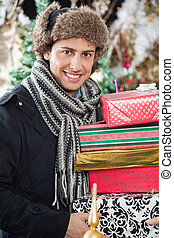 Happy Man Carrying Stacked Gift Boxes
