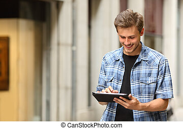 Happy man consulting online content in a tablet in the street