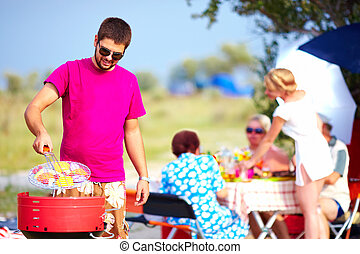 happy man cooks vegetables on the grill, family picnic