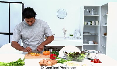 Happy man cutting vegetables in his kitchen