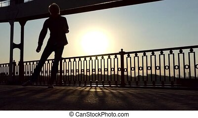 Happy Man Dances Disco, Jumps, at Sunset on a Bridge Over...