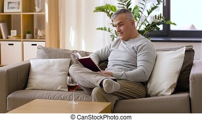 happy man drinking wine and reading book at home - leisure...
