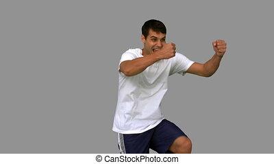 Happy man gesturing on grey screen in slow motion