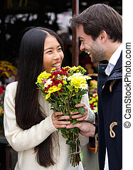 Happy man giving flowers to smiling woman